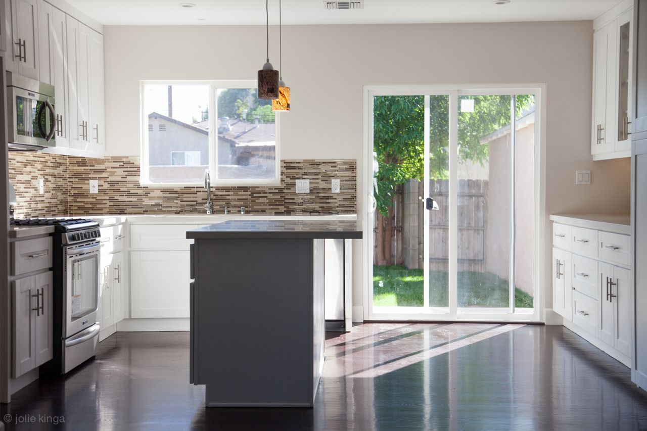 los angeles kitchen remodelling contractors with grey and white cabinets plus backsplashes and pendant lamps and wall oven plus glass windows