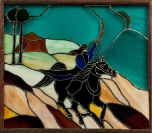 A framed stained glass piece of a bedouin rider and horse.