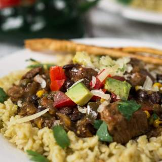 Poblano Pork Stew over Tomatillo Rice is rich in flavors and has a deliciously warm kick. It can be made in a crockpot or simmered on the stove. Either way, you're going to love this dish   HostessAtHeart.com