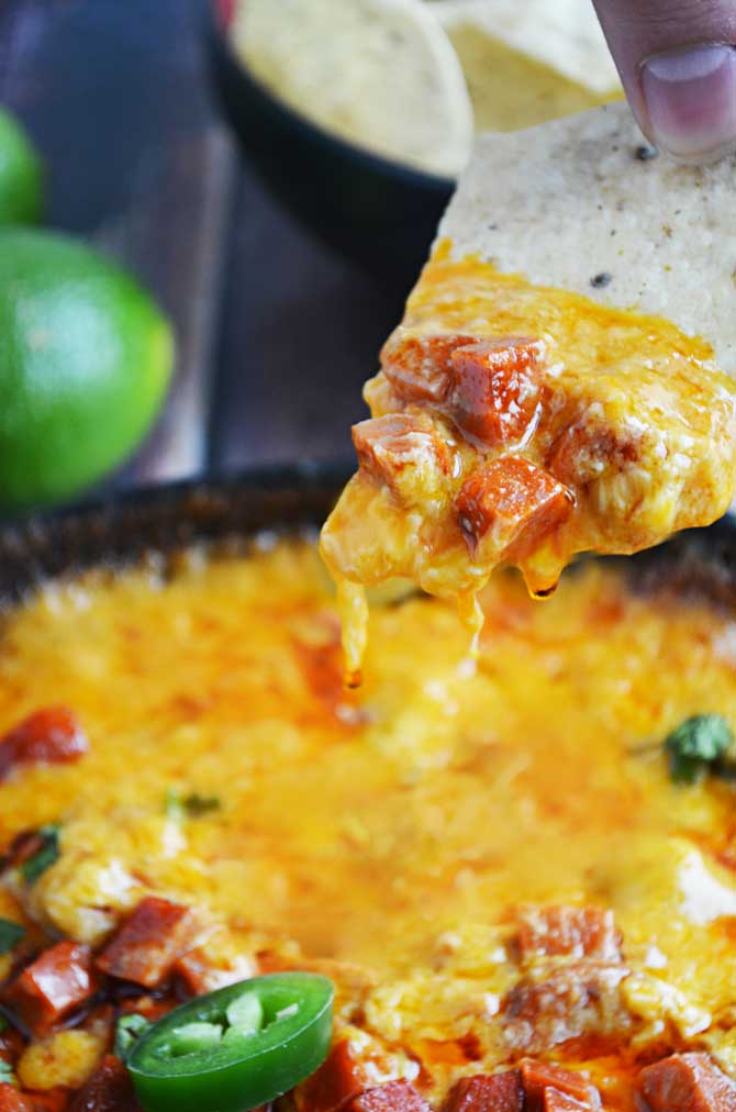 Chorizo Queso Fundido- a spicy Mexican cheese appetizer with  beer, spicy chorizo, roasted poblanos,  garlic, tomatoes, onions, and cilantro mixed in!  Need I say more?