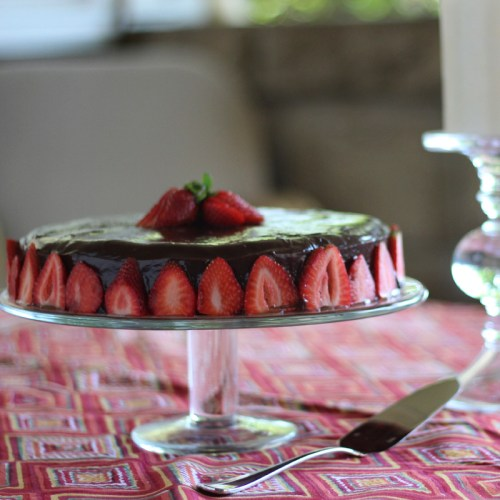 A gluten-free cake iced in ganache and decorated with strawberries