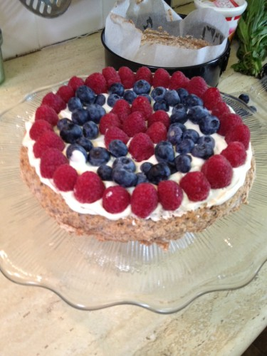 The bottom layer covered in cream and berries