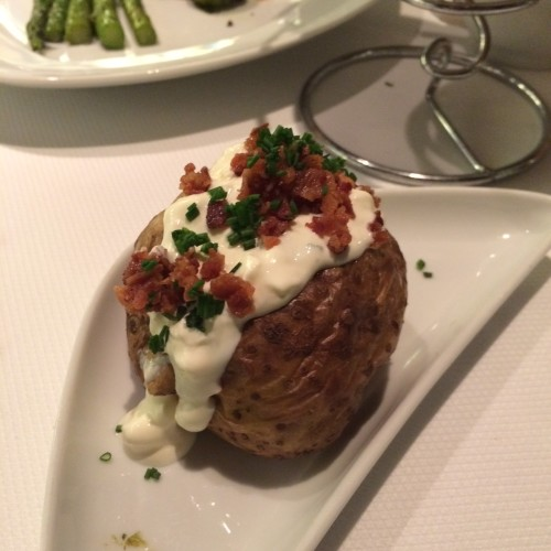 An Idaho jacket potato filled with sour cream, bacon and chives