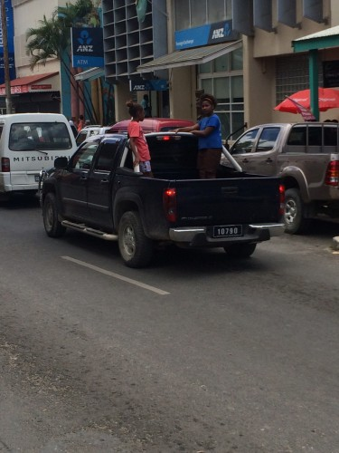 Two young girls just leaning out of a truck on the main street of Port Vila.