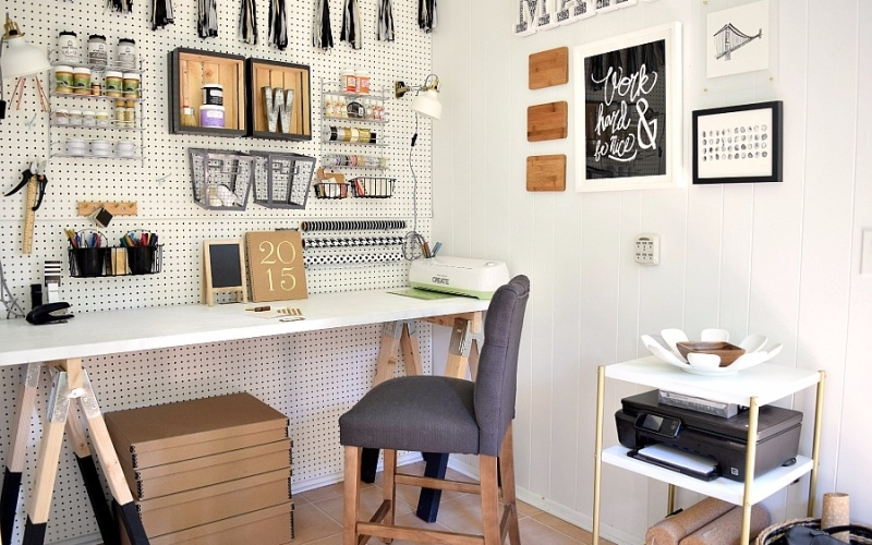 A completely DIY'd craft room that includes an organized pegboard, a DIY desk and a fun color on the ceiling.