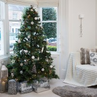 Snow white living room with Christmas tree in bay ...