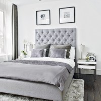 Modern bedroom with grey upholstered bed and soft ...