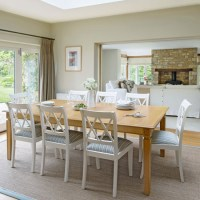 Light bright dining room with white painted chairs ...