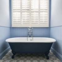 Traditional bathroom with blue roll top bath and shuttered ...