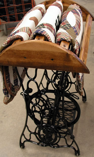 Antique sewing machine base turned quilt rack