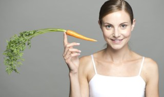 Young woman balancing carrot on fingertip