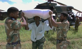 South African National Defence Force Army Captain O Khumalo (R) and Major S. Dlomo (L) help to unload maize for flood victims in Mozambique February 25. Aid workers battled fresh chaos across southern Africa on Friday and governments appealed for urgent international aid as floods cut the main road between Zimbabwe abd South Africa.  JN/FMS - RTR1MYK