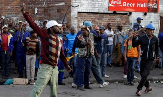 A crowd of anti-immigrant protesters demonstrate outside the Jeppe hostel in Johannesburg, South Africa, Friday, April 17, 2015, where some foreigners have sought refuge. Several shops and cars owned by foreigners were torched in downtown Johannesburg overnight in continued anti-immigrant attacks. (AP Photo/Themba Hadebe)