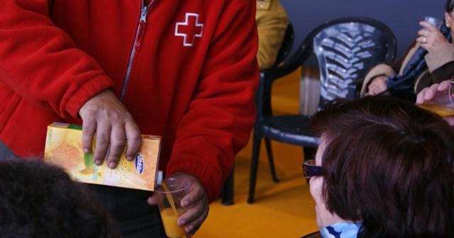 Un miembro de Cruz Roja reparte zumo.