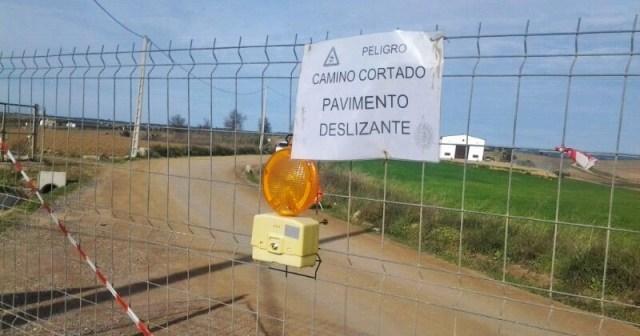 Un cartel advierte del peligro de un camino.