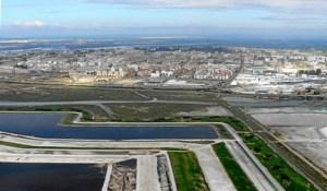 Vista aérea de las balsas de fosfoyesos con la ciudad de Huelva al fondo. (Rodolfo Barón)