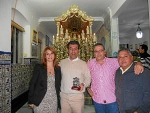 Ante la Carreta y con el Simpecado, la Hermana Mayor, Carmen Prieto, el Vicepresidente, Paco Moreno, y el Vicetesorero, Tomás Remedios, acompañan a Fernando Romero.