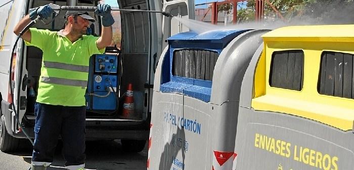 Un operario de Giahsa limpia un grupo de contenedores en Isla Cristina