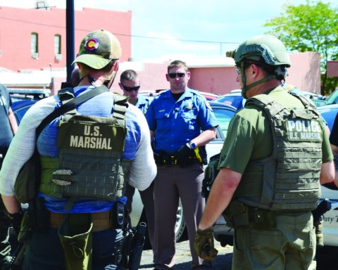 Deputy US Marshals brief local and state law officers on a search operation they were preparing to launch in the CR 520 area Saturday afternoon.  Federal agents were trying to find a Huerfano County resident who allegedly cut off his federal court issued electronic monitoring device Friday evening, before disappearing, leaving personal items and a suicide note behind at his home.  The individual, who was free on a pre-trial release on a federal charge relating to child pornography, was not found.  Local lawmen HCSOCaptain Milan Rapo (far left) and WPDOfficer Joe Deatherage (far right) listen to the briefing before a convoy of vehicles began the trip to the northwest part of the county.   Photos by Eric Mullens.