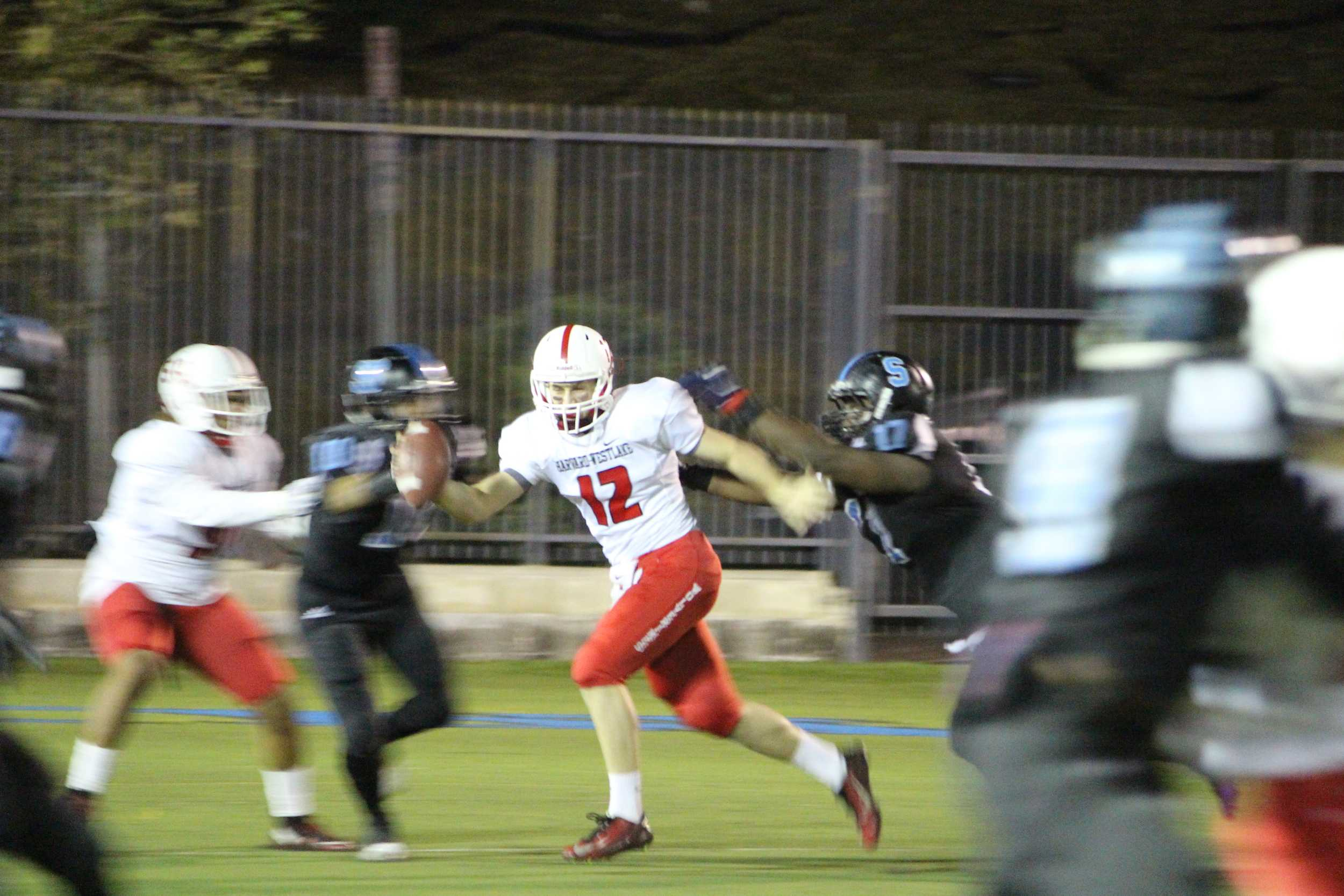 Quarterback Noah Rothman '16 scrambles out of the pocket as he is chased by the Salesian defensive line.