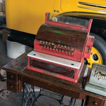 Dad's cash register and check writer sit on Mom's treadle sewing machine. Men chased the buck, while women stayed home and sewed. That's how it once was, folks, like it or not.