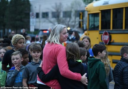 A teacher embraces young students in a parking lot near the STEM School Highlands Ranch in Colorado on Tuesday after a shooter opened fire