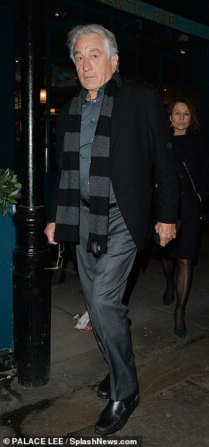 Dapper:Robert wore a dark green shirt which he paired with grey trousers, a black and grey striped scarf and a black coat