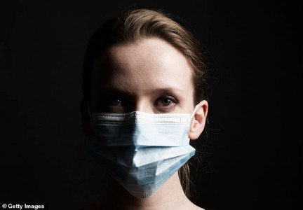 A woman pictured with a medical mask covering her face. The only reason to wear a mask in public is if you think you are infected – to protect others (file photo)