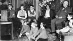 Family Sitting Around Listening To Radio