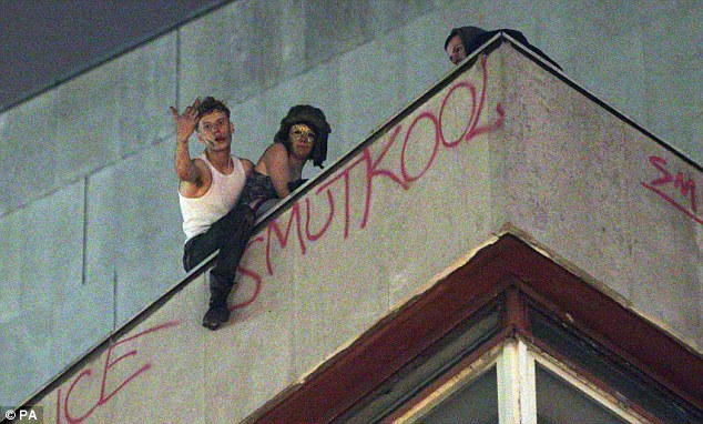 Anti-social: A raver balances over a ledge as he gestures at crowds gathered outside the Halloween rave
