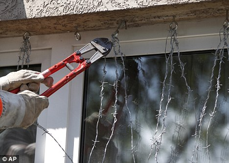 Sealed up: Police remove the barbed wire from a window at Fischer's flat
