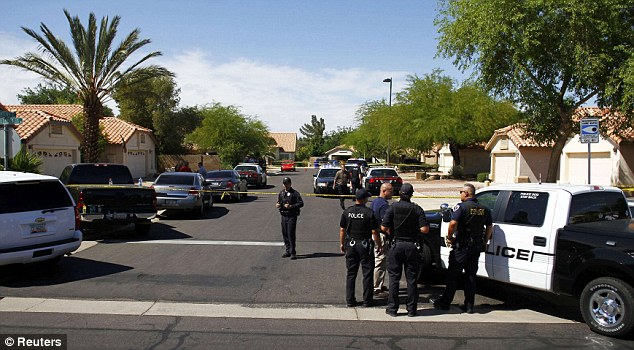 Police officers look over the scene of a shooting in a residential area of Gilbert, Arizona May 2, 2012. Local newspapers reported five people killed