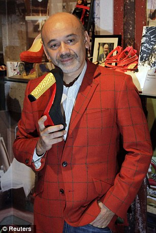Sole trader: The French shoe designer Christian Louboutin poses with some of his creations at the Design Museum in London