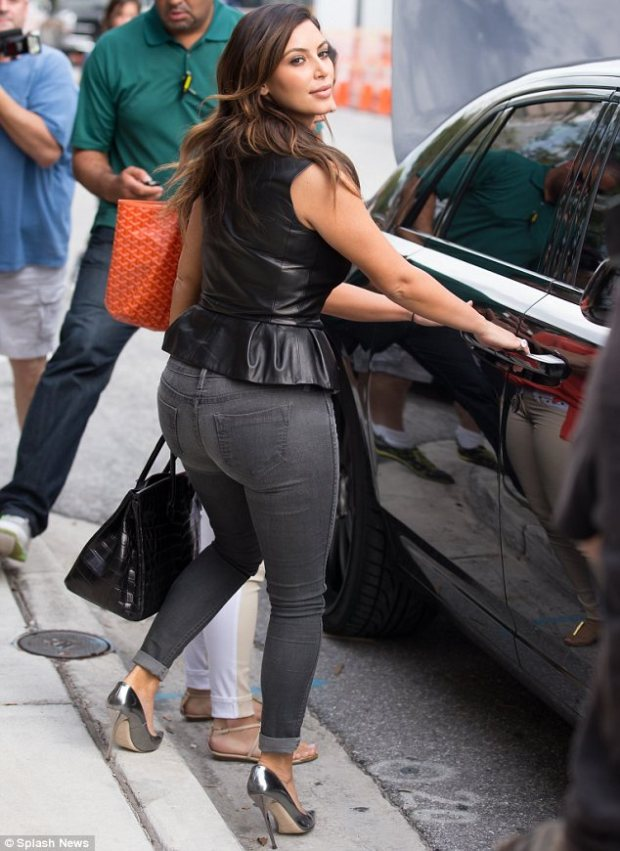 Feeling cheeky as usual: Kim couldn't resist showing off her famous derriere for the cameras