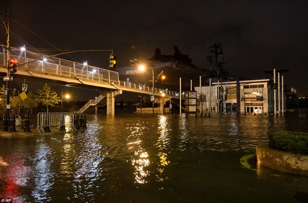 Ship: This photo by Dylan Patrick shows flooding along the Westside Highway near the USS Intrepid, background centre, as Sandy moves through the area