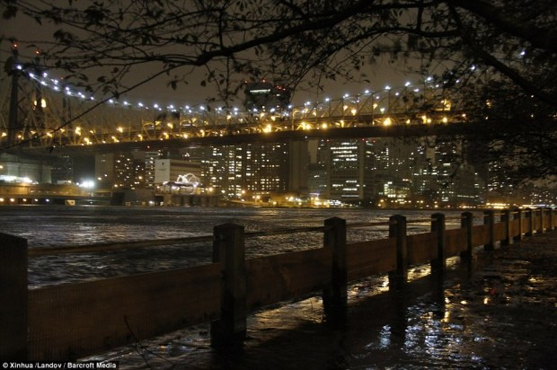 City landscape: The Queens Bridge and flooded shore is pictured on Roosevelt Island in New York City on Monday night