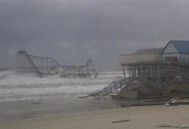 After the storm: The iconic Jersey Shore boardwalk is bent and twister, with parts totally destroyed, while the tar Jet rollercoaster is hanging into the Atlantic ocean
