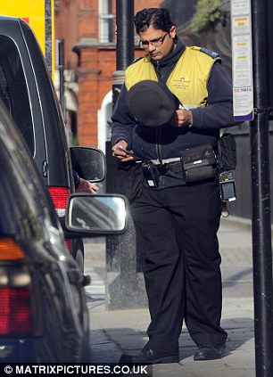 A London traffic warden is spotted accepting a £20 note in exchange for allowing a day's parking in central London