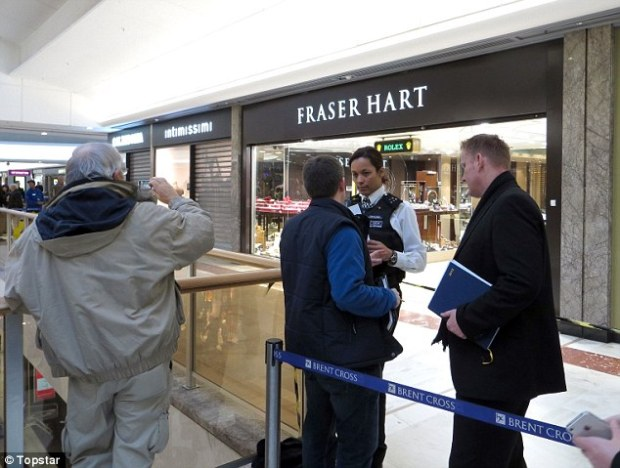 Probe: Police officers and security guards from the shopping centre quickly closed off the crime scene as hundreds of shoppers looked on amazed