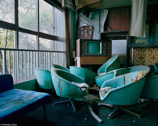 Bygone era: A smattering of green leather chairs and a vintage television clutter a hotel lounge