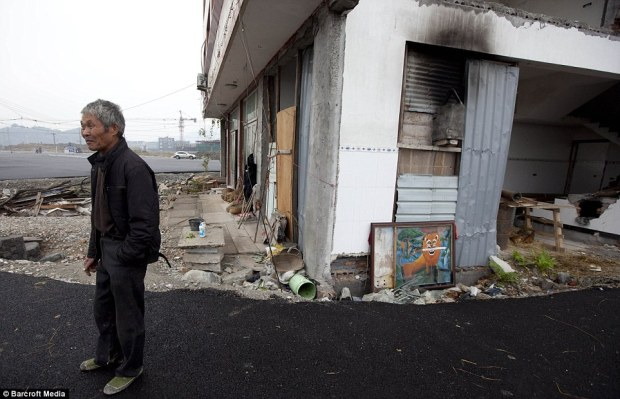 Folorn: Mr Baogen looks wistfully across his new scenery, the tarmac from the new road waving haphazardly along the side of the building and demarcating the homeowner's land