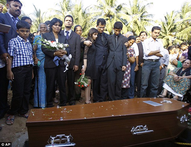 Mourning: Ben Barboza (centre) holds his son Junal, on his right, and daughter Lisha at the burial of his wife