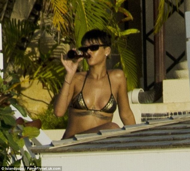 Having a good time and enjoying single life: Rihanna enjoyed several beers as she soaked up the sun in Barbados on Tuesday at her in a luxury beach front villa