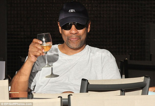 Cheers! Denzel Washington looked pretty happy with his lot as he raised a glass of wine on a yacht in St Barts on Thursday