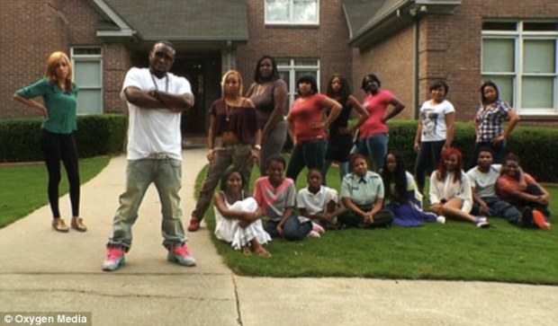 Controversial: Rapper Carlos 'Shawty Lo' Walker, with his 11 children (sat) and their ten respective mothers and his 19-year-old girlfriend (left) - who are all set to star in a new TV show titled All My Babies' Mamas