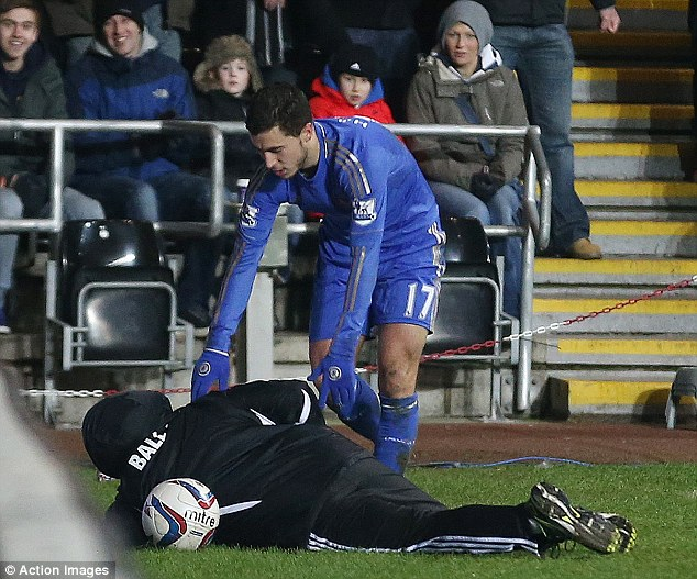 Grabbed: Hazard reaches for the football as the ballboy writhes on the ground