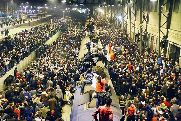 Desperation: Thousands of desperate supporters trying to board a train after fleeing from the stadium