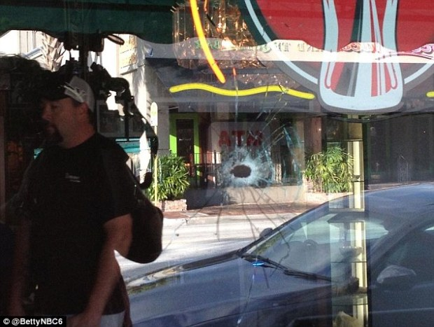 The scene: Bullet holes could be seen in the glass windows of nearby buildings in pictures tweeted by local news reporters