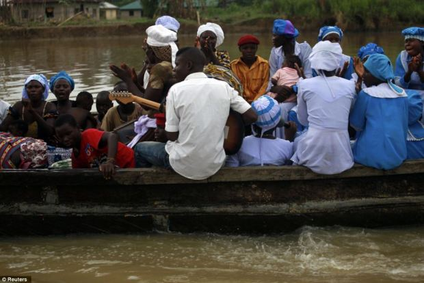 A canoe conveys members of a Christian sect as they sing and conduct a church service on the River Nun