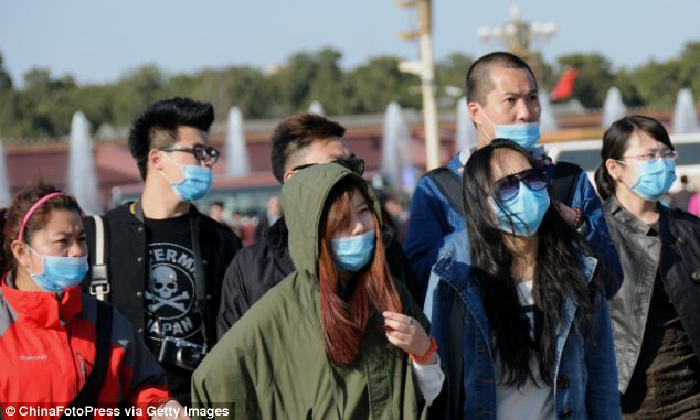 Tourists wear masks as a precaution walk in Tiananmen Square